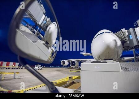 Night over A380 aircraft on stand at airport, reflected in wing mirror of ground crew vehicle - Stock Photo