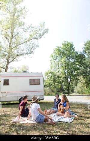 Group of young adults sitting on picnic blanket , relaxing, camper van in background - Stock Photo