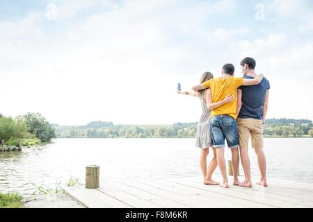 Three young adults standing on jetty, taking self portrait, using smartphone, rear view - Stock Photo
