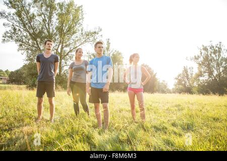 Portrait of group of friends, standing in field - Stock Photo