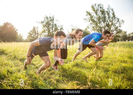 Group of friends running, racing, in field - Stock Photo