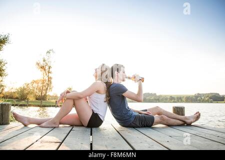 Young couple relaxing on jetty, sitting back to back - Stock Photo