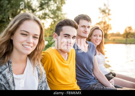 Portrait of group of friends sitting beside lake, smiling - Stock Photo