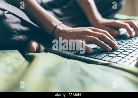 Cropped view of mid adult woman sitting cross legged on bed typing on laptop computer - Stock Photo