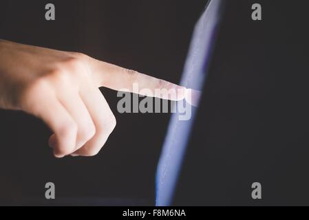 Side view of hand pointing at computer screen - Stock Photo