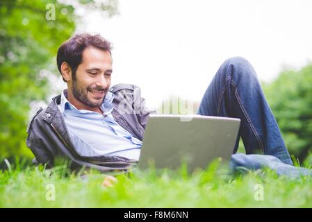 Young man lying on grass using laptop computer looking down smiling - Stock Photo