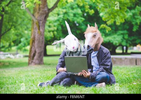 Young couple sitting on grass wearing rabbit and horse costume masks holding laptop computer - Stock Photo