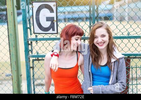 Young women standing beside sports ground, London, UK - Stock Photo