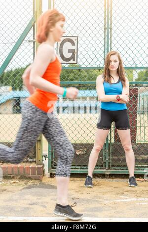 Runner passing young woman standing beside sports ground, London, UK - Stock Photo