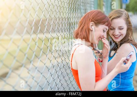 Young women using smartphone beside fence, London, UK - Stock Photo
