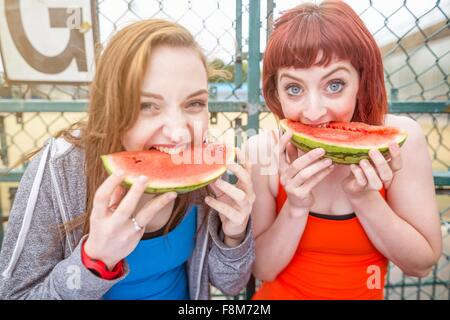 Young women eating watermelon beside sports ground, London, UK - Stock Photo