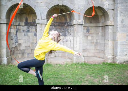 Young woman practising ribbon dance, walled arches in background - Stock Photo