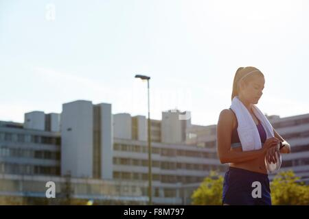 Young female runner checking smartwatch on urban rooftop - Stock Photo