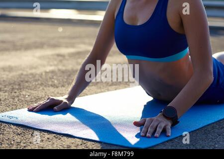 Cropped view of young woman practicing yoga in urban parking lot - Stock Photo