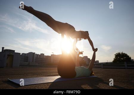 Two silhouetted young women practicing yoga in urban parking lot - Stock Photo
