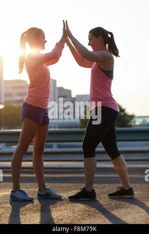 Two young women giving each other high five on rooftop - Stock Photo
