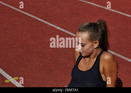 Young female runner sitting on race track - Stock Photo