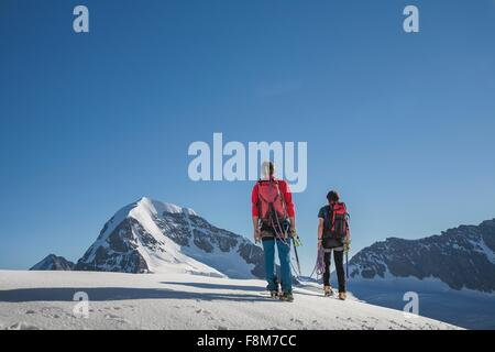 Rear view of two male climbers moving up, Canton Bern, Switzerland - Stock Photo
