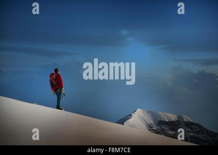 Male climber standing on ridge looking out,  Canton Bern, Switzerland - Stock Photo