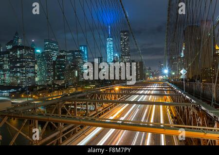 Elevated view of Brooklyn bridge and Manhattan financial district skyline at night, New York, USA - Stock Photo