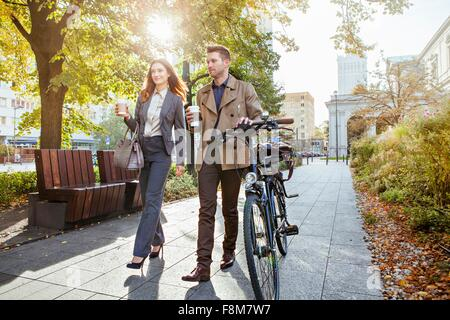 Casual businessman and woman pushing bike through park - Stock Photo