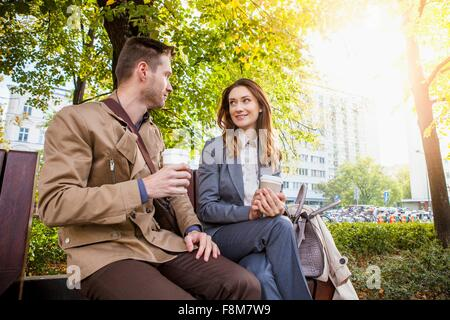 Casual businessman and woman in park with coffee - Stock Photo