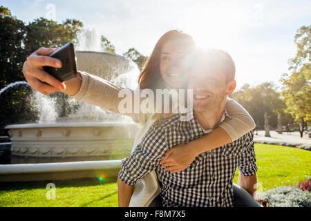 Woman taking selfie having a piggy back in park - Stock Photo
