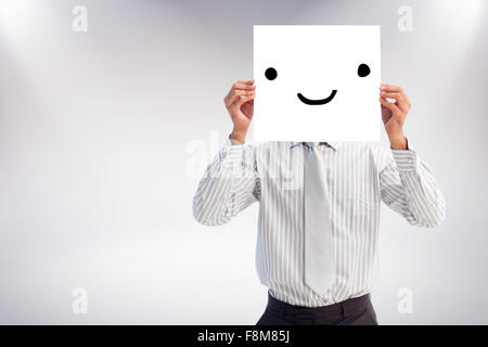 Composite image of businessman holding a white card covering his face - Stock Photo