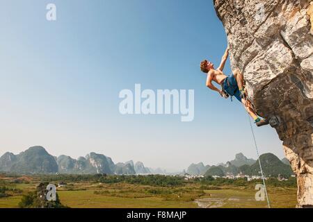 Male climber climbing on the Egg - a limestone cliff in Yangshuo, Guangxi Zhuang, China - Stock Photo