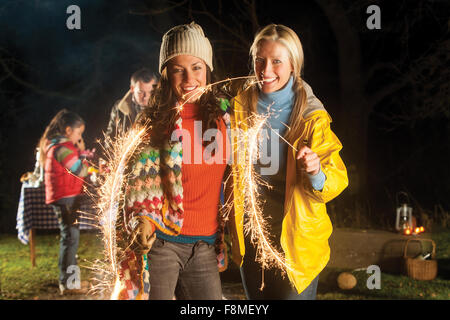 Two women are standing together smiling for the camera with lit sparklers in their hands. - Stock Photo