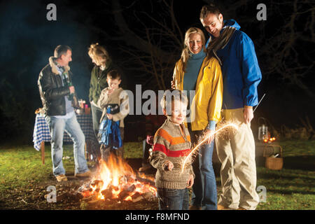 Family in garden enjoying a bonfire and playing with sparklers - Stock Photo