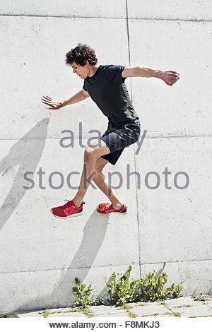 Young man free running against concrete wall - Stock Photo