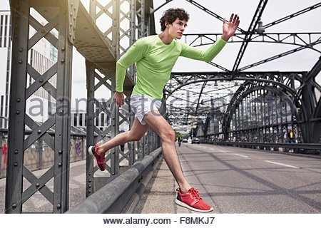 Young man free running on urban bridge - Stock Photo