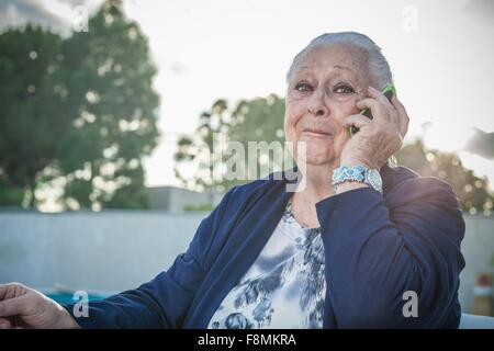 Senior woman using smartphone in backyard - Stock Photo