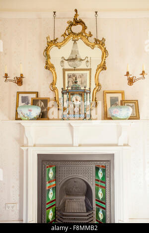 The home of designer Erica Pols. The fireplace in the master bedroom. A mirror and patterned decorated china and - Stock Photo