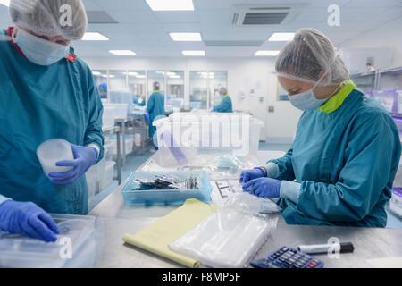 Workers packing surgical instruments in clean room of surgical instruments factory - Stock Photo
