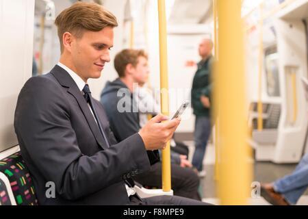 Businessman texting on tube, London Underground, UK - Stock Photo