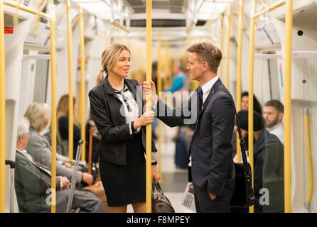 Businessman and businesswoman talking in tube, London Underground, UK - Stock Photo