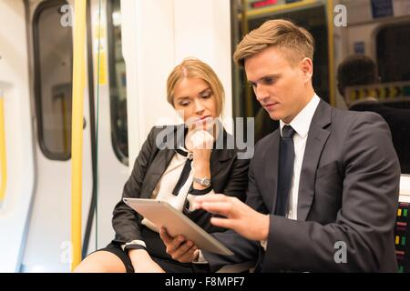 Businessman and businesswoman sharing digital tablet, London Underground, UK - Stock Photo