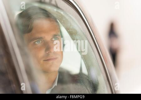 Businessman looking out of car window - Stock Photo