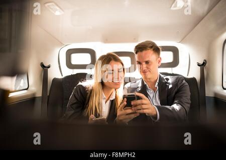 Businessman and businesswoman using smartphone in black cab, London, UK - Stock Photo