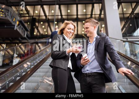 Businessman and businesswoman on escalator, London, UK - Stock Photo