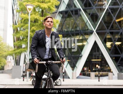 Businessman on bike, 30 St Mary Axe in background, London, UK - Stock Photo