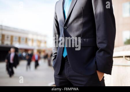 Businessman with hands in pocket, partially obscured, London, UK - Stock Photo