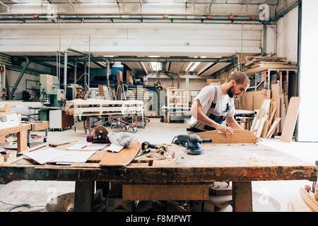 Young man in carpentry workshop looking down sanding skateboard - Stock Photo