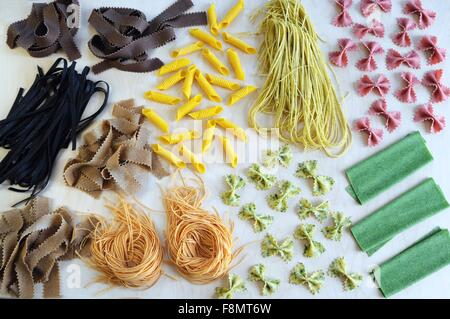 An arrangement of various colourful types of pasta - Stock Photo