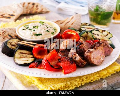 Grill platter with lamb, peppers, aubergines, courgettes, a hummus dip and pita bread - Stock Photo