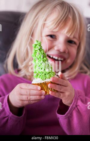 A young girl holding a Christmas tree cupcake in both hands - Stock Photo