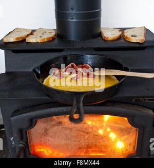 Eggs and Bacon Cooking in a Cast Iron Skillet on a Wood Burning Stove; Bread Toasting on the Stove - Stock Photo