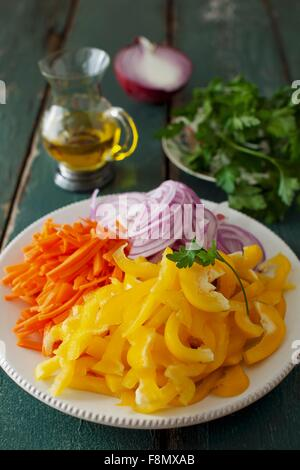Sliced Yellow Pepper, Carrots and Red Onion on a White Plate - Stock Photo
